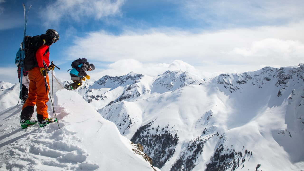 Silverton Ski Area Skiers Dropping Cornice Colorado