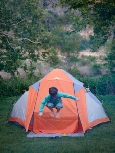 Camping with Kids Checklist Child Jumping in Tent