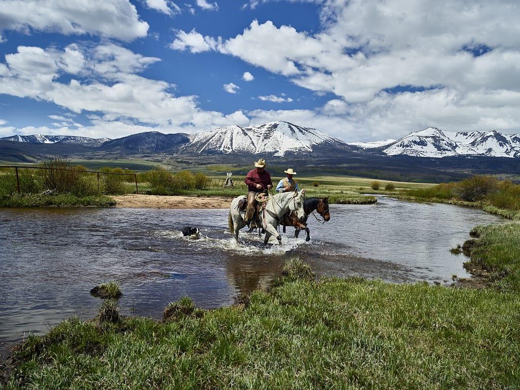 Cowboys on Horseback Cross North Platte River in North Park Colorado