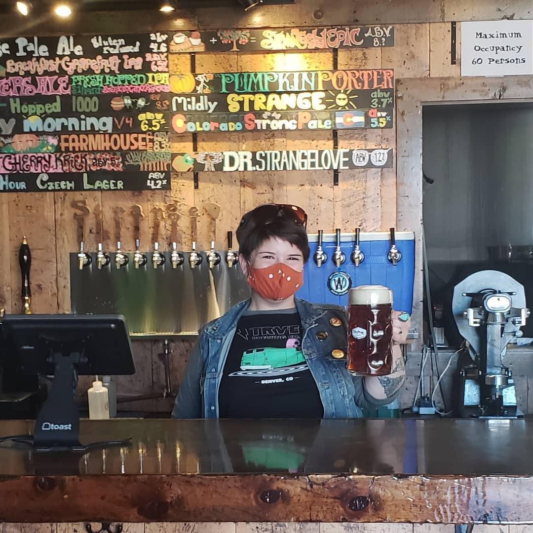 Strange Craft Beer Company Denver CO Bartender holding beer
