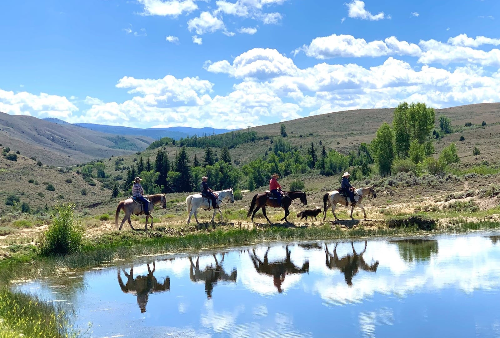 Image of four horseback riders near a pond at Bar Lazy Jay Guest Ranch, CO