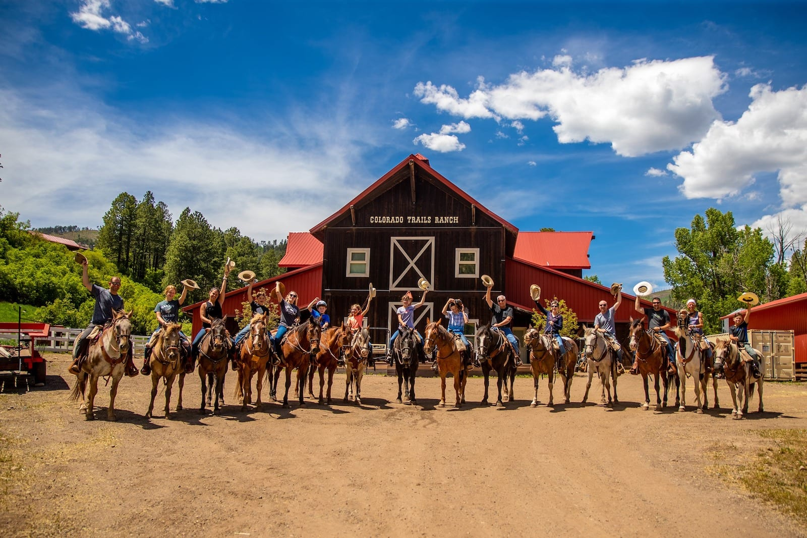 Image of visitors on their horses, raising their hats at Colorado Trails Ranch, CO