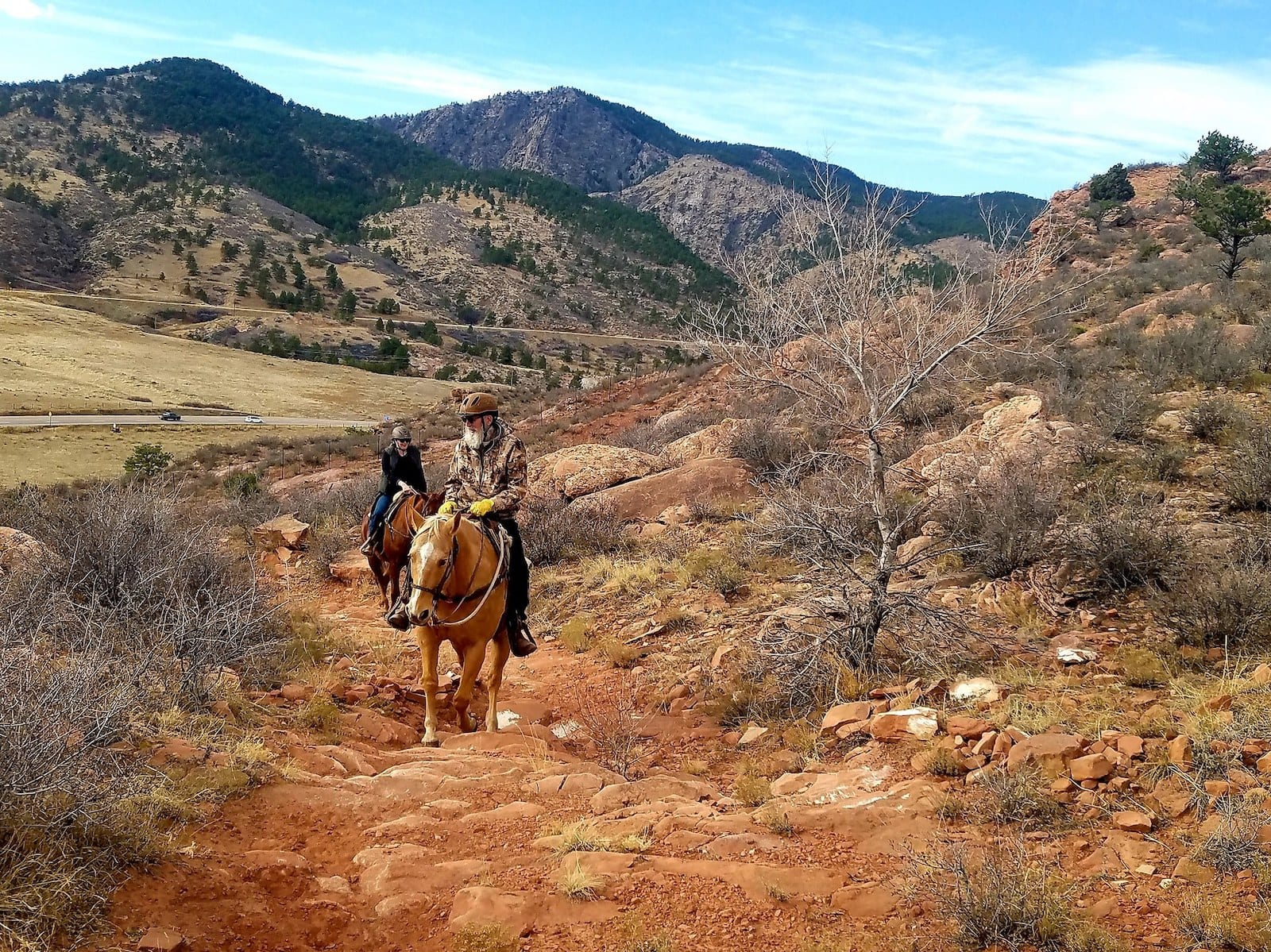 Image of two horseback riders on a trail at Sylvan Dale Guest Ranch, CO