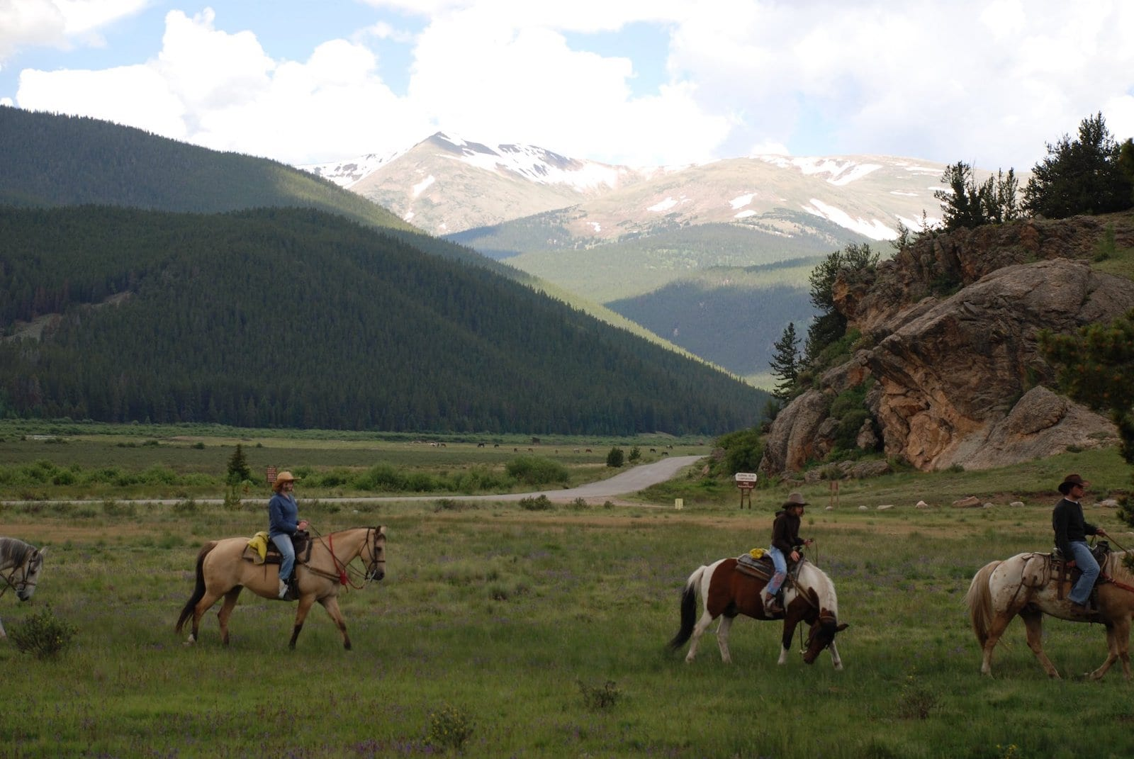 Image of people riding horses in a valley at Tumbling River Ranch, CO
