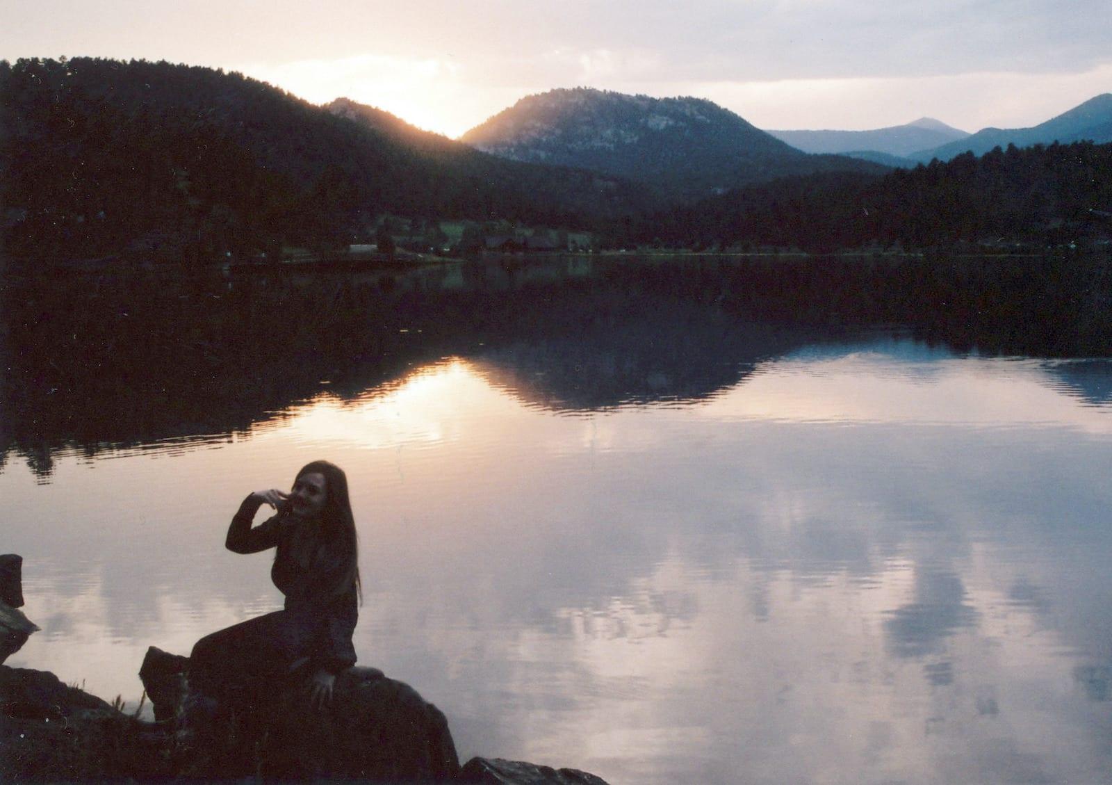 Woman sitting beside Evergreen Lake Colorado