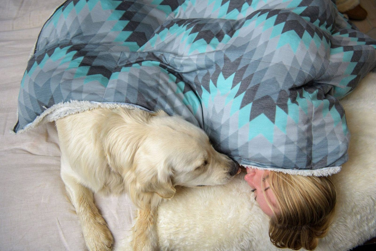 Image of a woman snuggling with her dog in a Holden & Hay weighted blanket