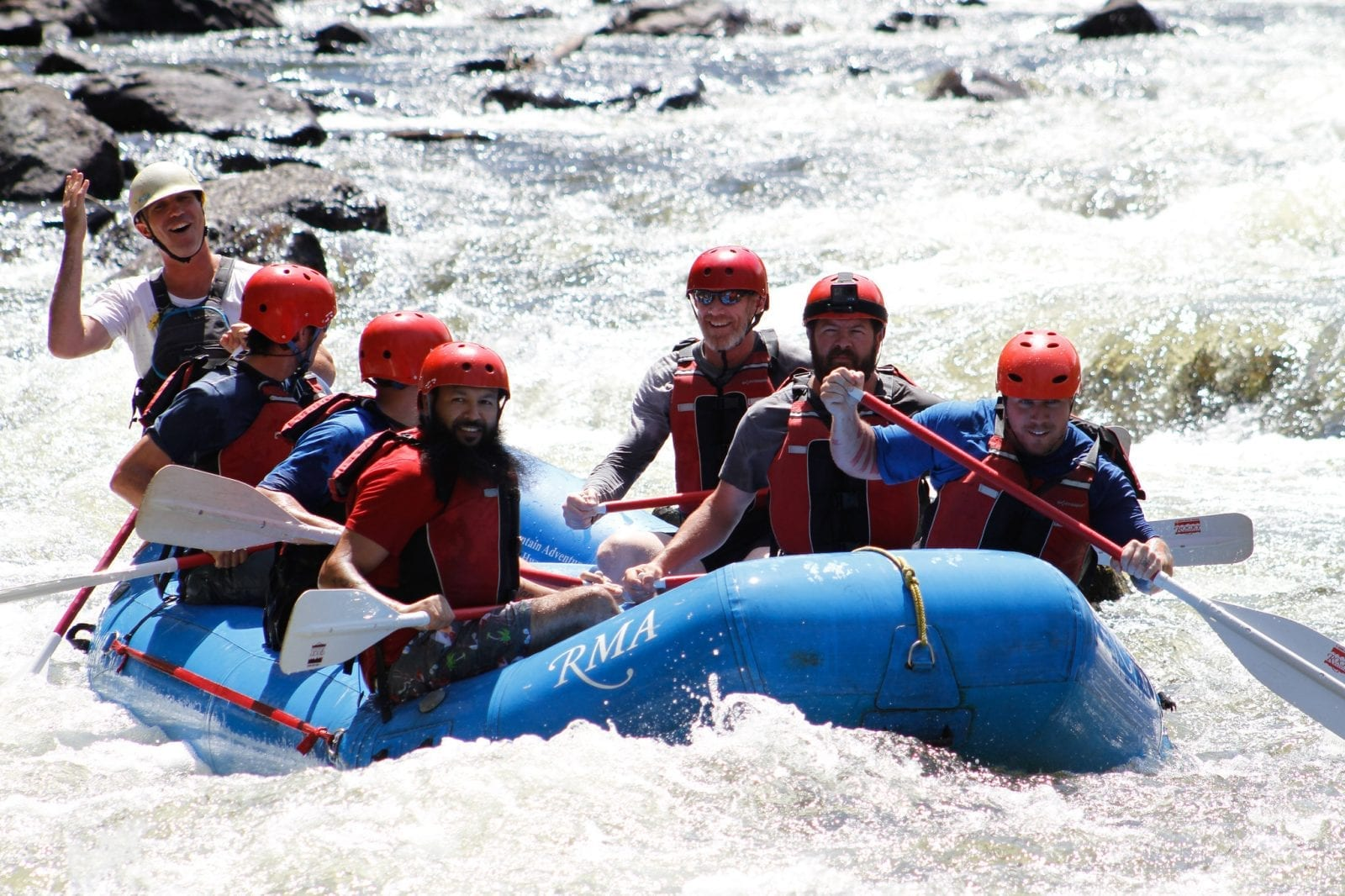 Image of 6 men whitewater rafting on cache la-poudre river in colorado