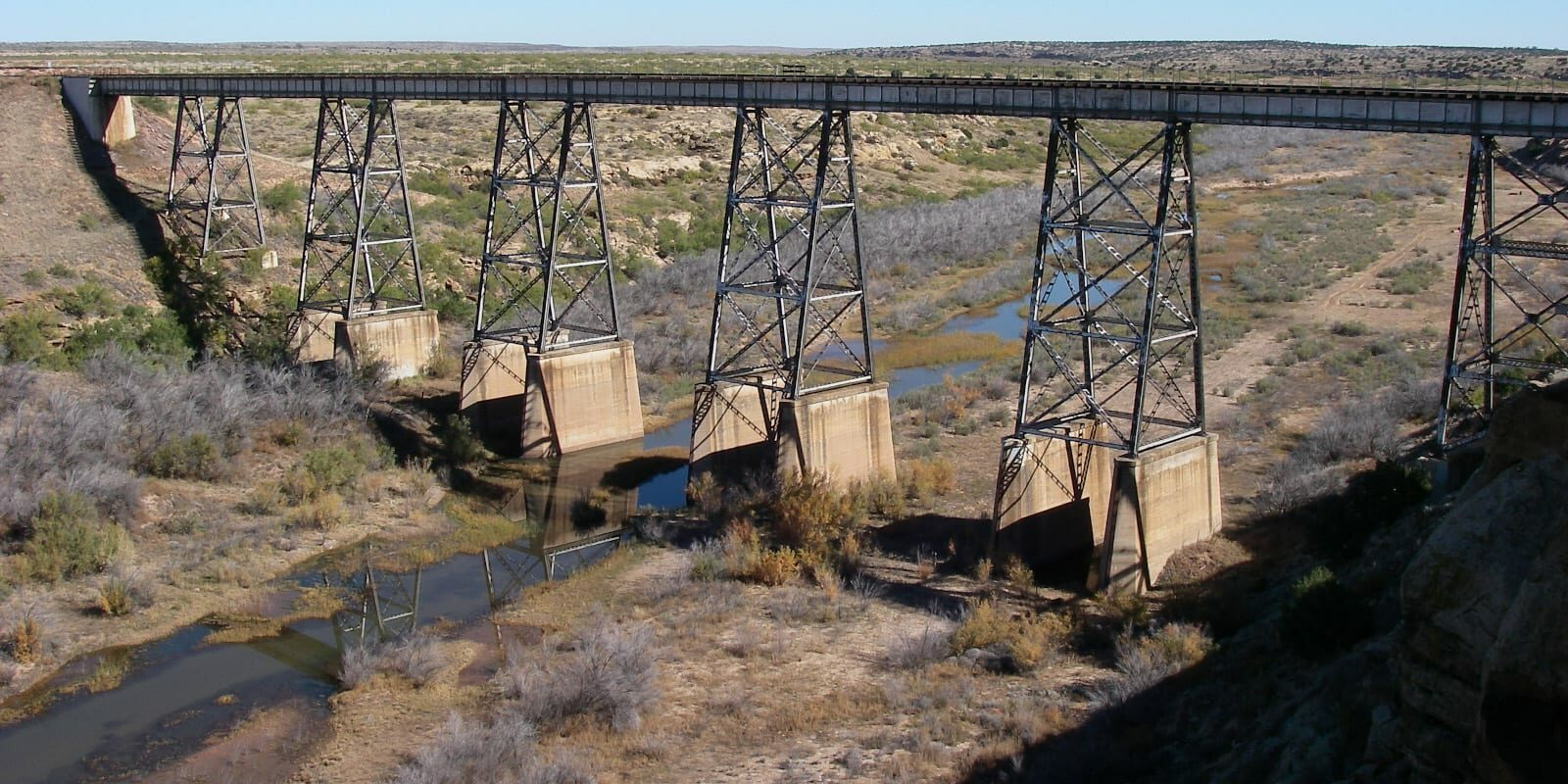 Image of the Canadian River in New Mexico with a railroad bridge crossing over