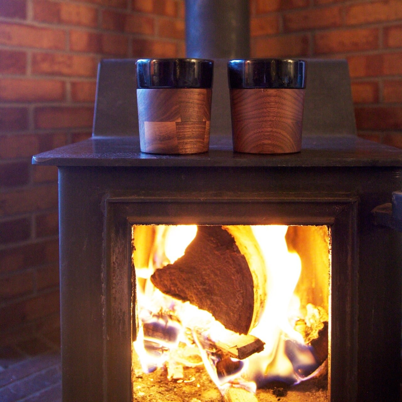 Image of two David Rasmussen wooden cups over a fireplace