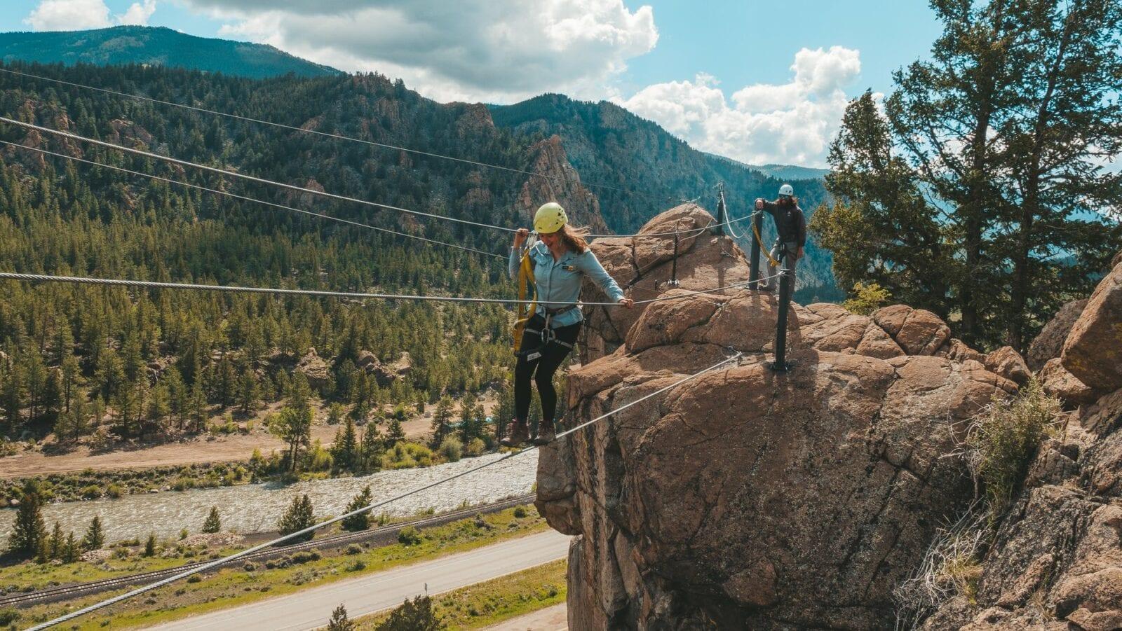 Image of a woman on a cable bridge on the Granite Via Ferrata course in Buena Vista, Colorado