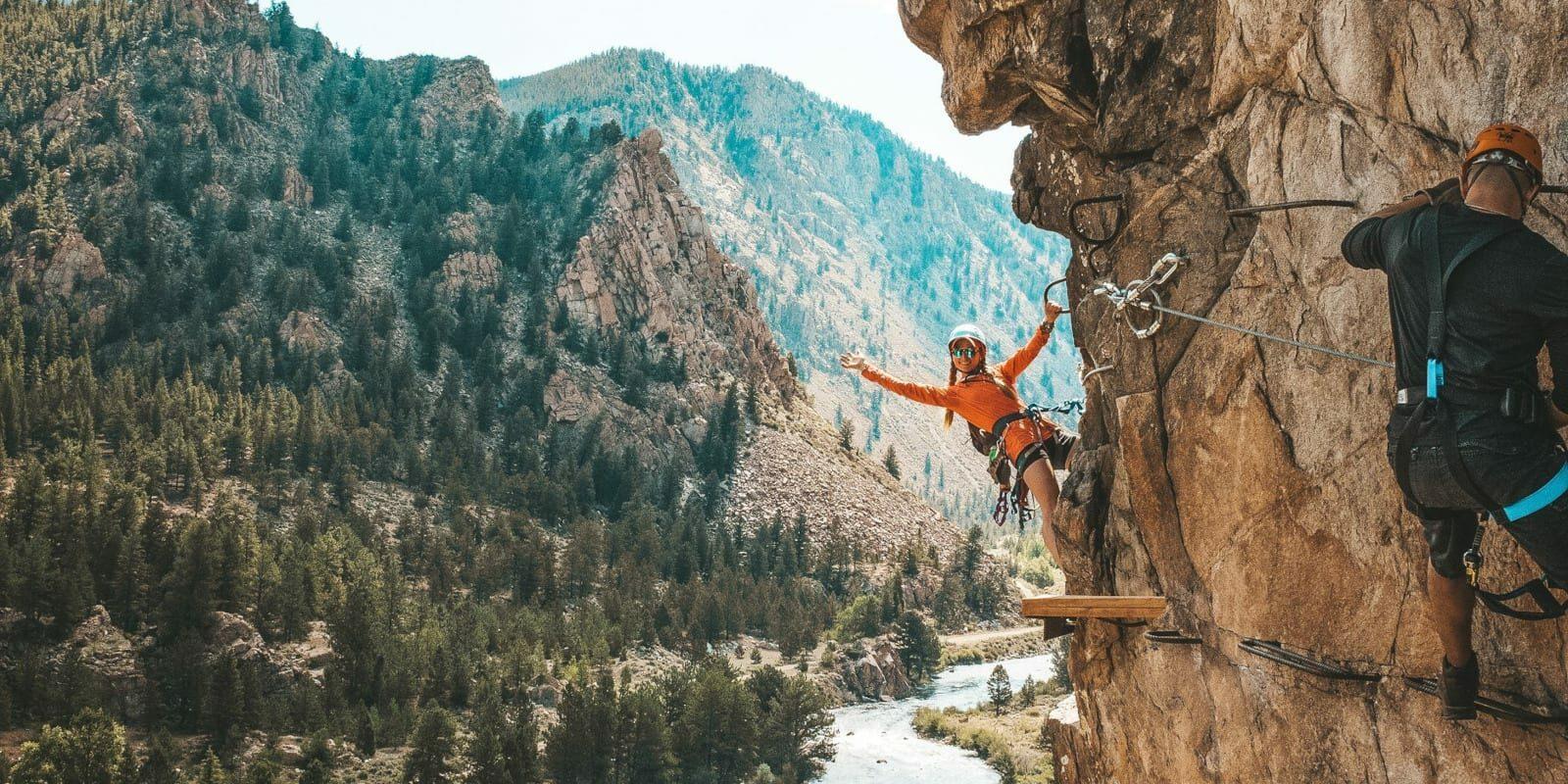 Image of a woman on the Granite Via Ferrata hanging off the cliff in Buena Vista, Colorado