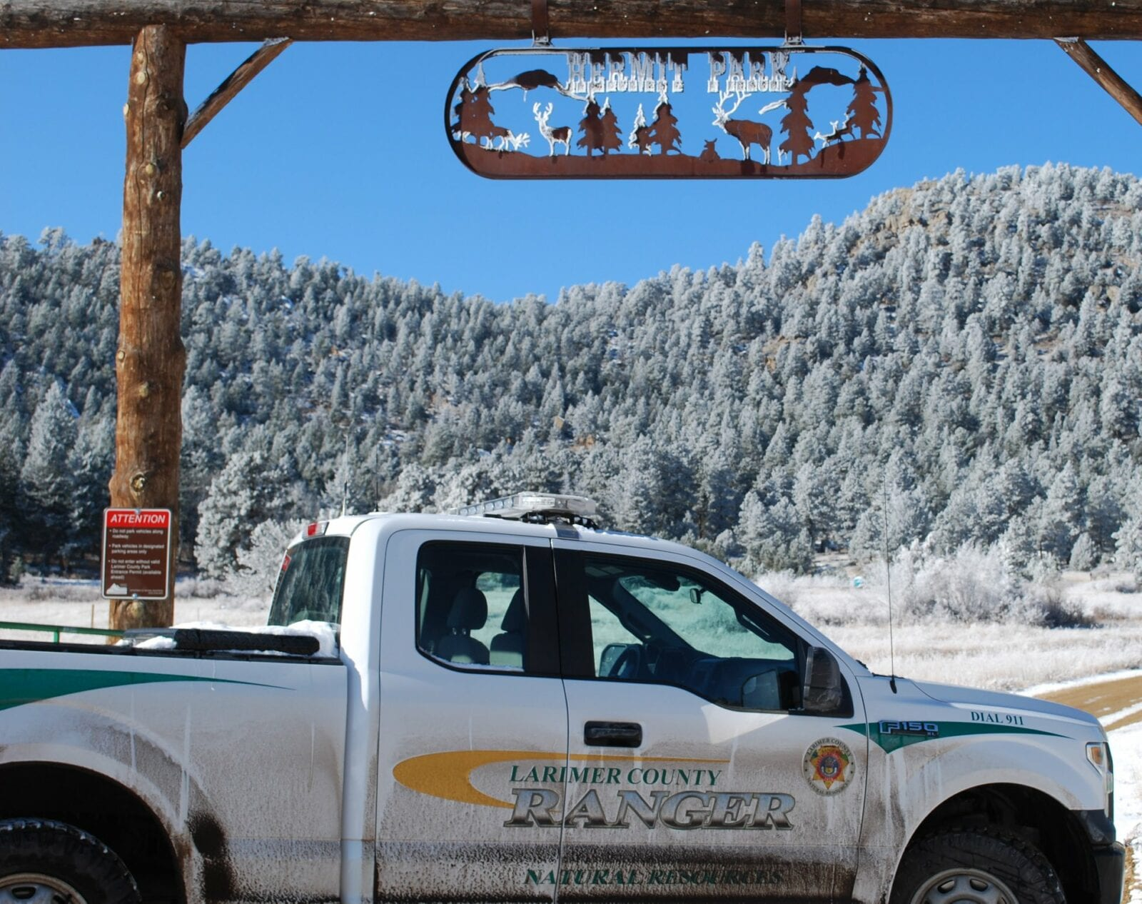 Image of a ranger car in front of the Hermit Park sign in Estes Park, Colorado