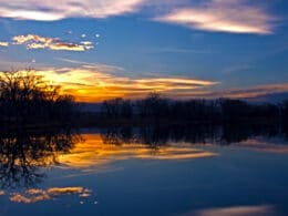 Image of the sunset reflecting on the water at at Riverbend Ponds Natural Area in Fort Collins, Colorado