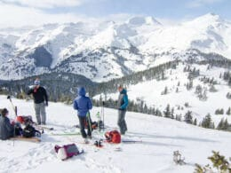 Image of skiers and snowboarders enjoying a drink at the top of Bluebird Backcountry in Colorado