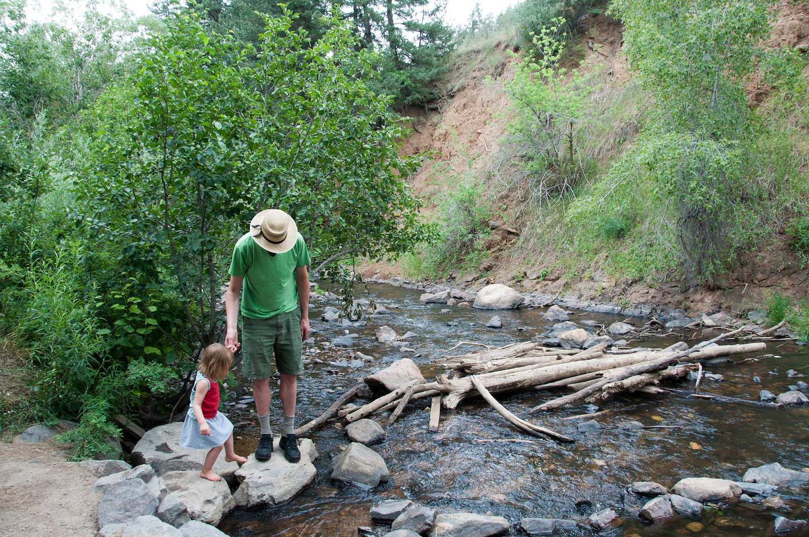 Image of a father and child crossing a creek at Lair o' the Bear Park in Idledale, Colorado