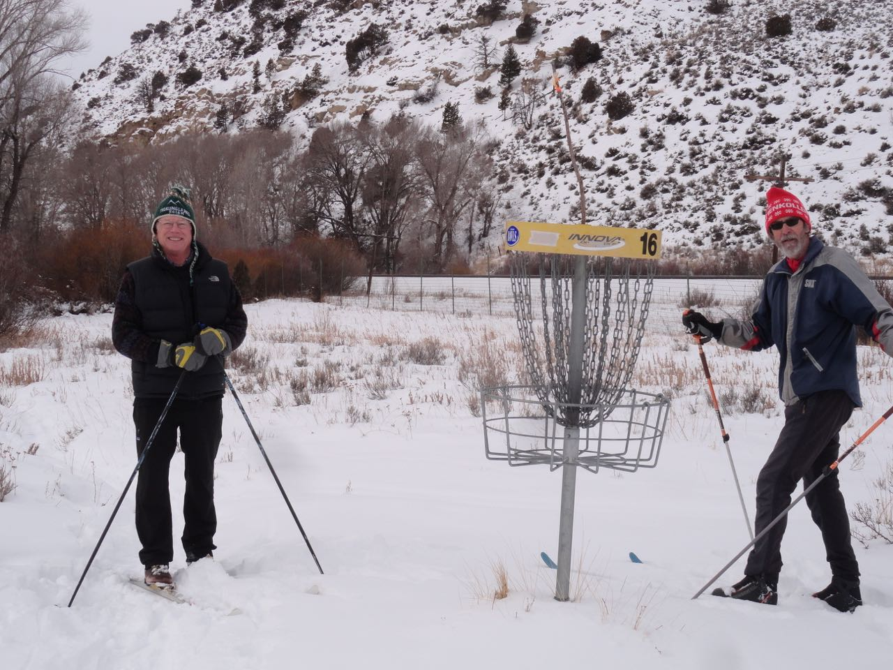 Image of two men playing disc golf in winter at