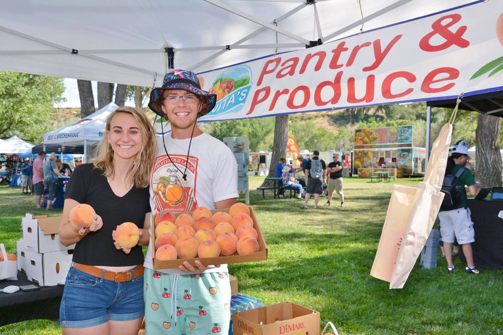 Image of two people at a produce stand holding peaches a the Palisade Peach Festival in Colorado