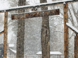 Image of the Bar Lazy J Guest Ranch entrance sign covered in snow