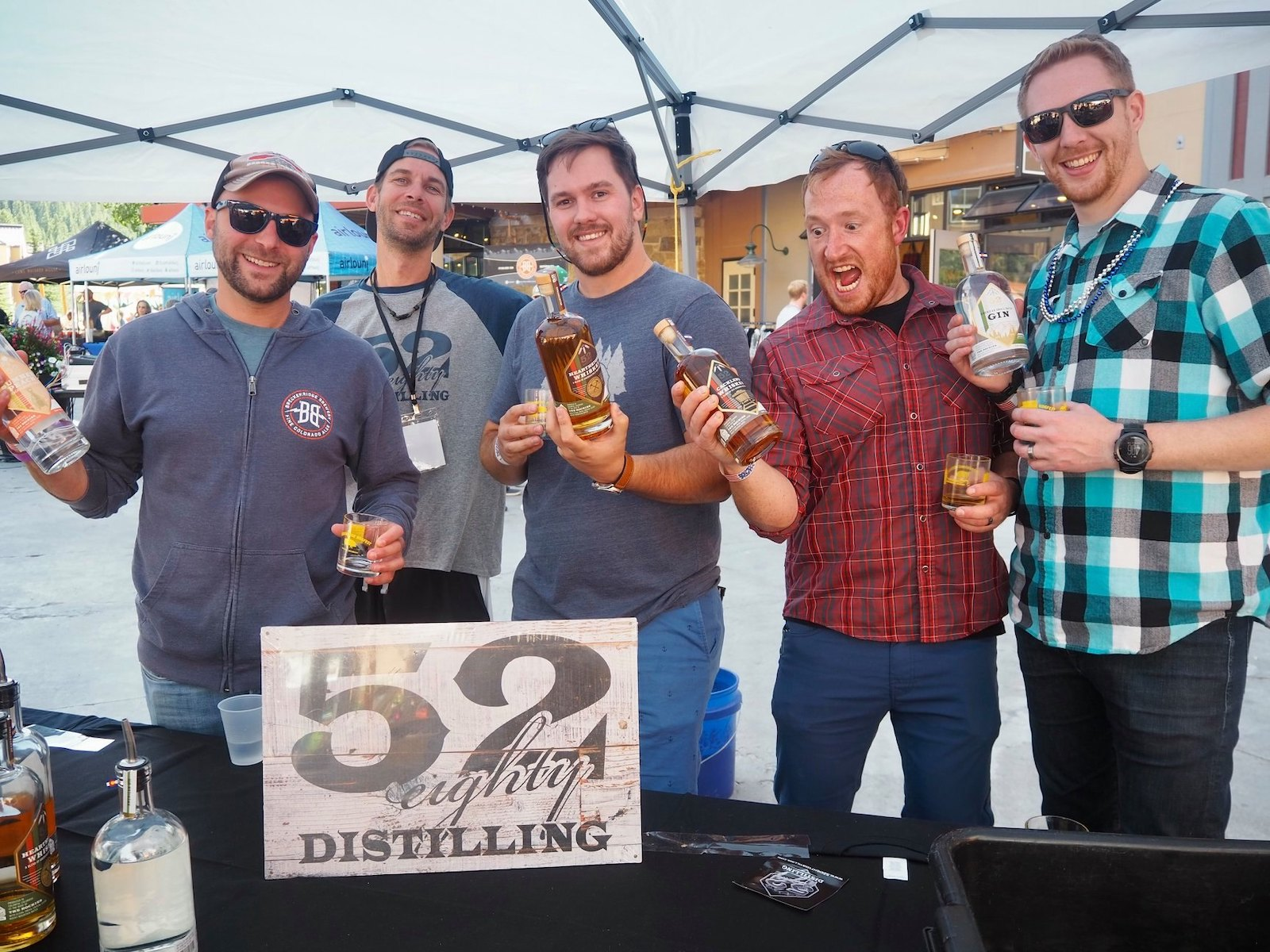 Image of a group of men at the 52 Eighty Distilling booth at Breckenridge Hogfest in Colorado