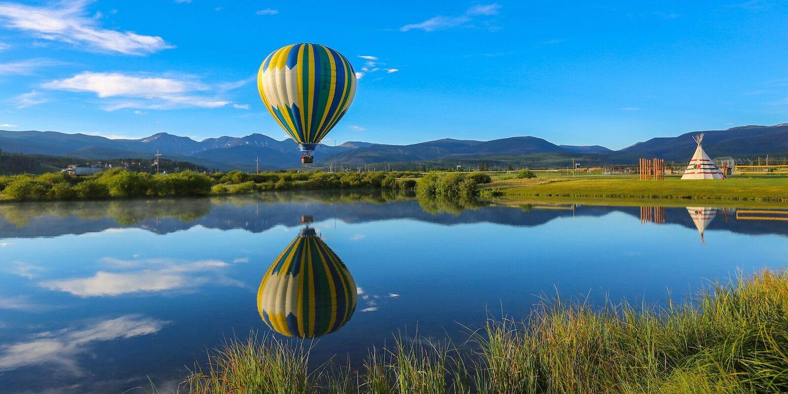 Image of a Grand Adventures Balloon Tours hot air balloon over water in Fraser, Colorado