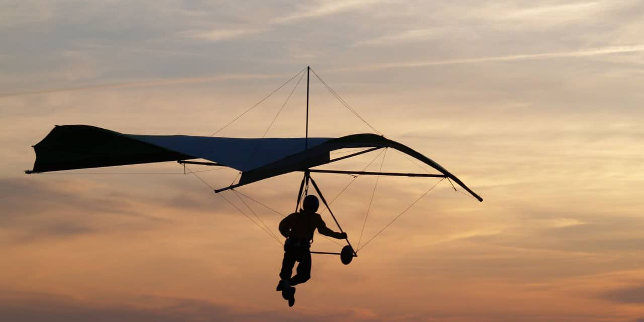 Image of a person hang gliding during sunset