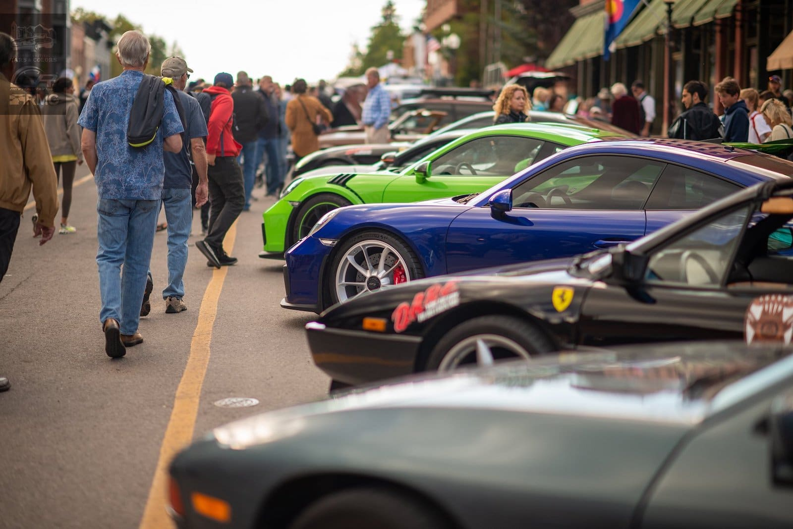 Image of people strolling past cars at the Telluride Autumn Classic in Colorado