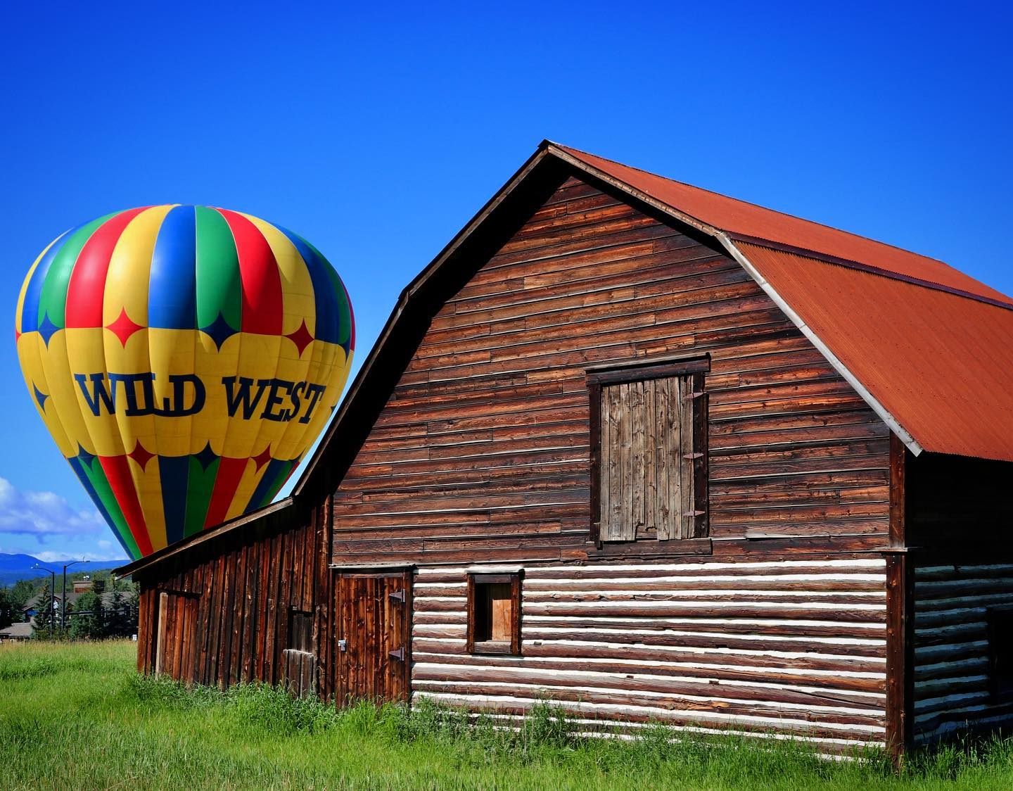 Image of the Wild West Balloon Adventures balloon behind a barn