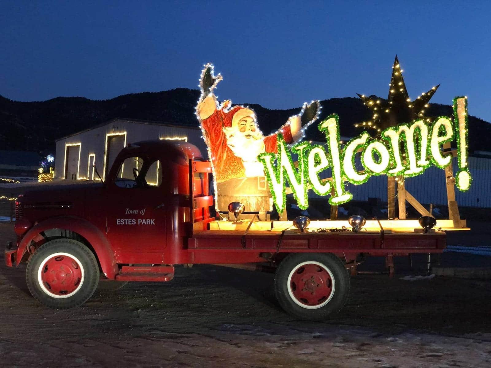 Gambar trik merah dengan tanda selamat datang santa yang menyala di Estes Park, Colorado