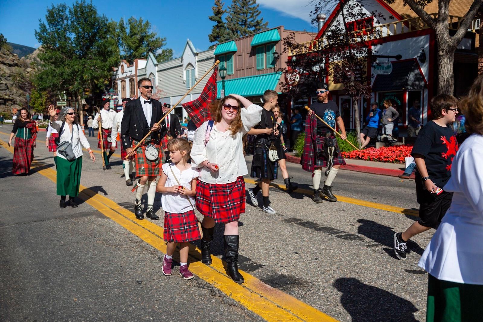 Gambar orang berjalan di parade Festival Dataran Tinggi Skotlandia-Irlandia Long's Peak di Estes Park, Colorado