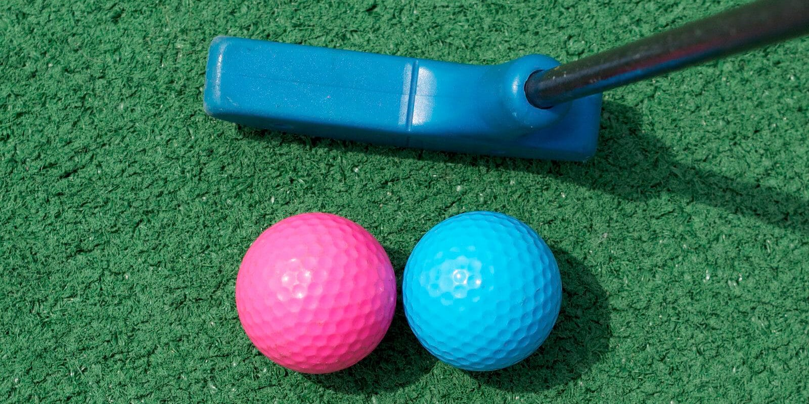 Image of a pink and blue golf ball and blue putter