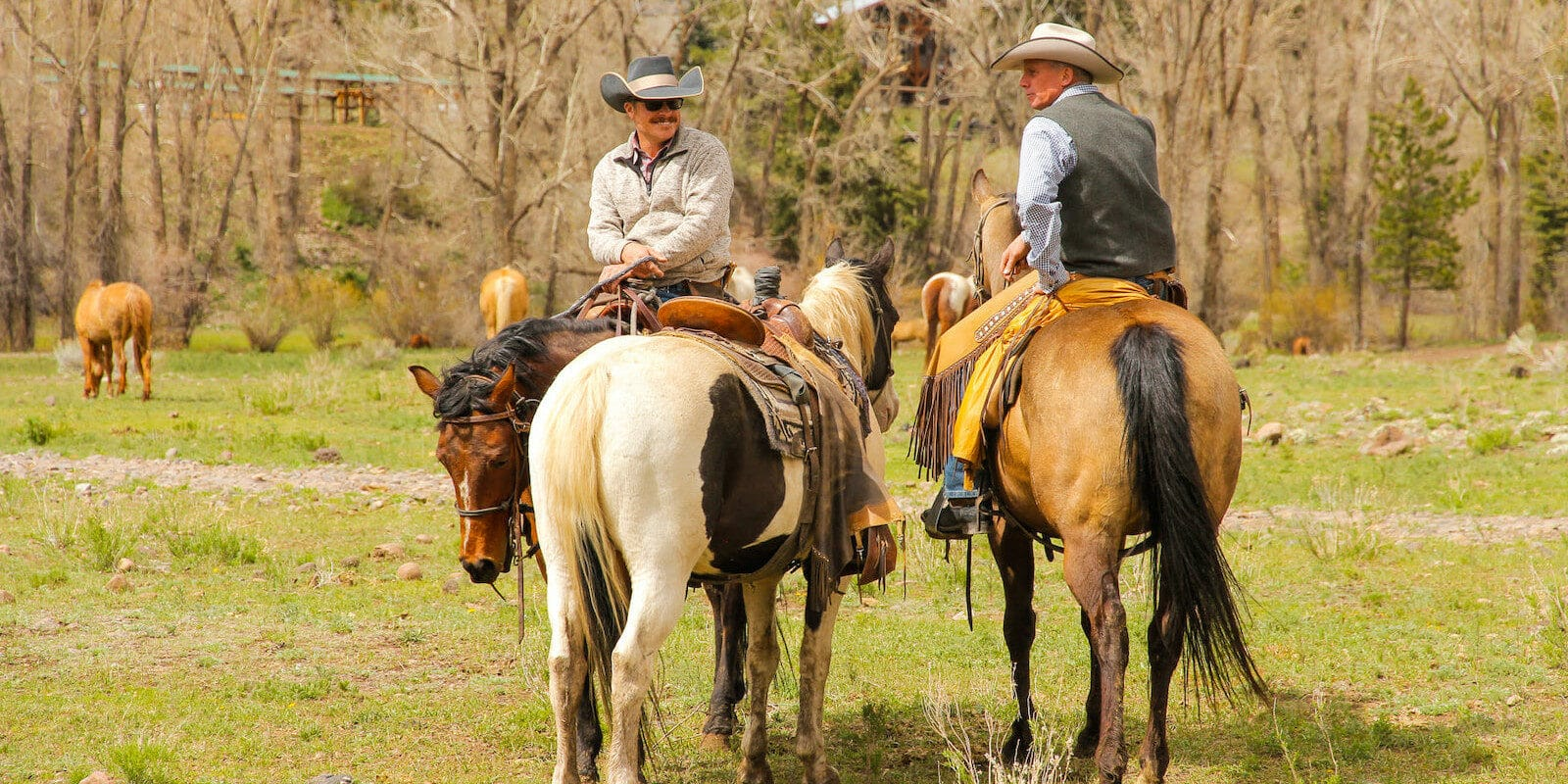 Image of two men riding horses at Rainbow Trout Ranch in Antonito, CO
