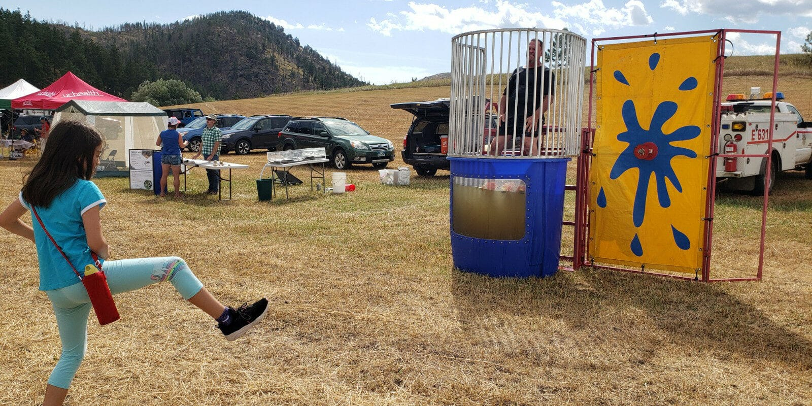Image of a girl throwing a ball at a dunk tank at the Rist Canyon Volunteer Fire Department Mountain Festival in Bellvue, Colorado