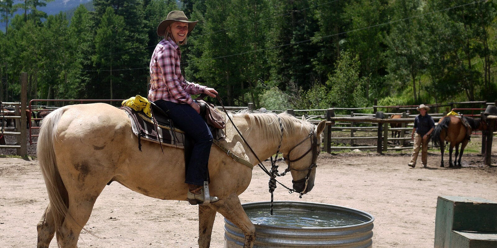 Image of a woman riding a horse at Tumbling River Ranch in Grant, Colorado