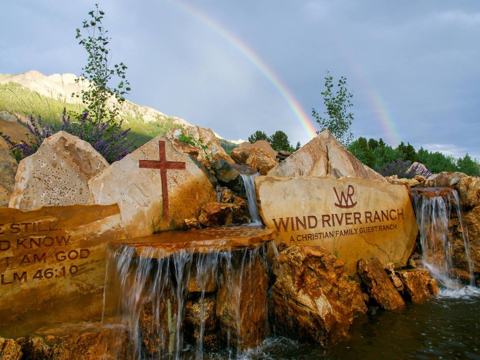 Image of the Wind River Ranch sign carved into a stone waterfall