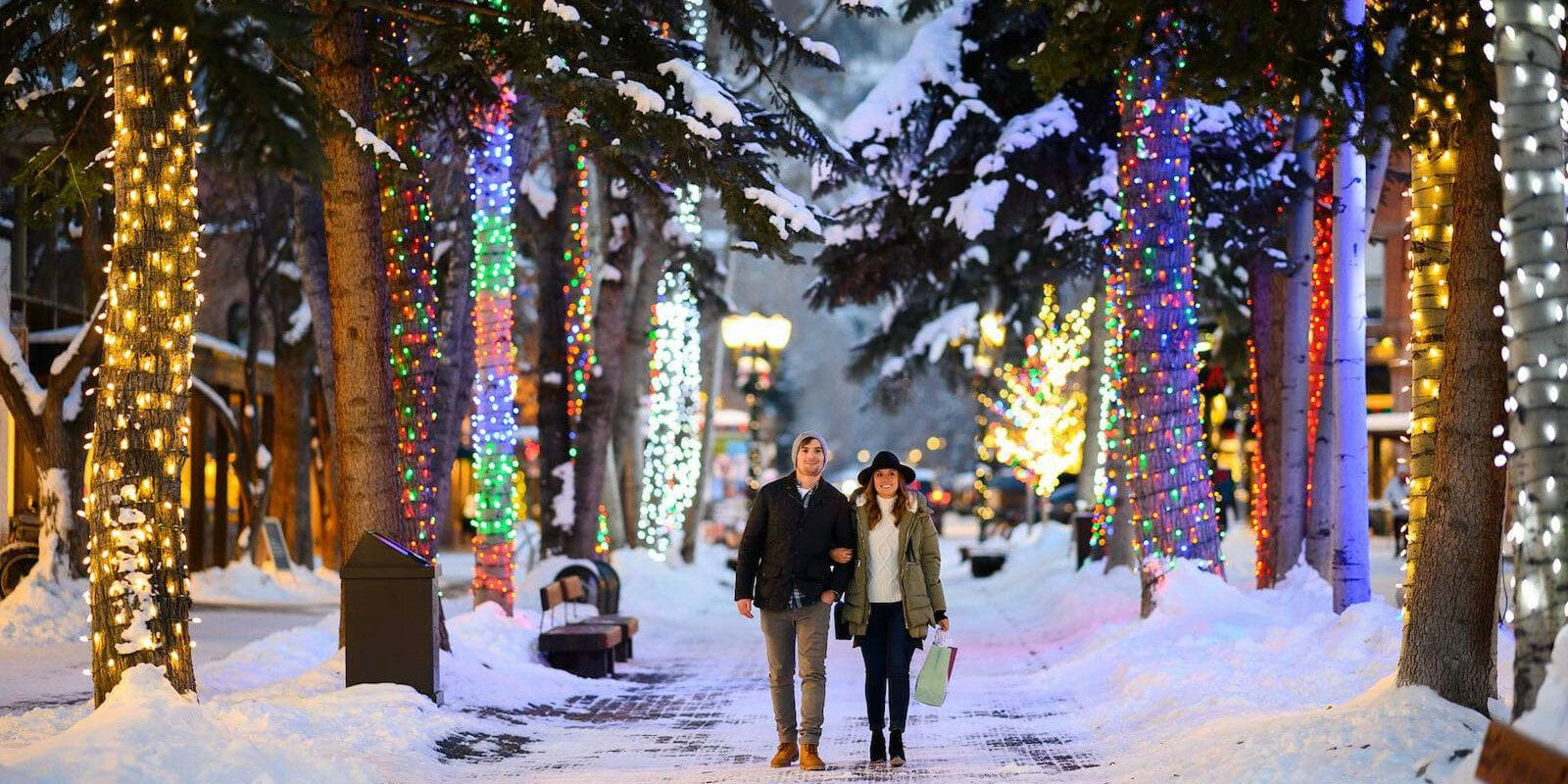 Image of a couple walking down a lane between illuminated trees during the holidays in the snow