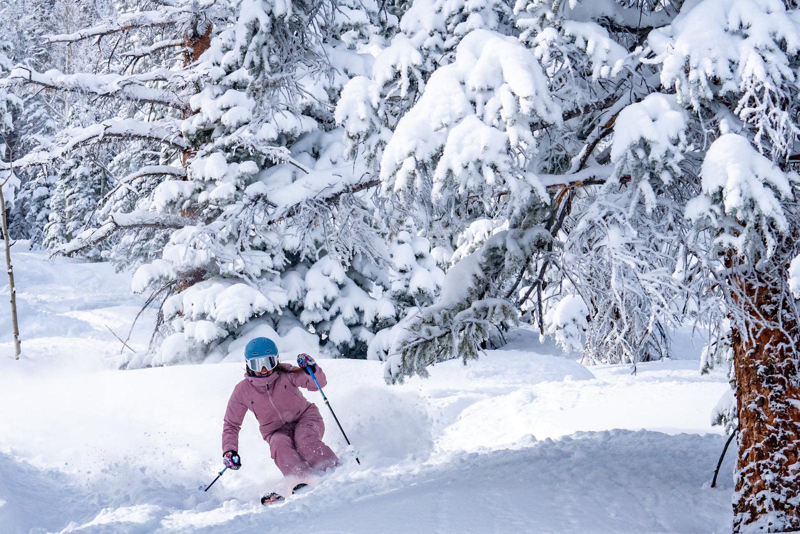 Gambar seorang pemain ski berbaju merah muda di Aspen Snowmass di Colorado