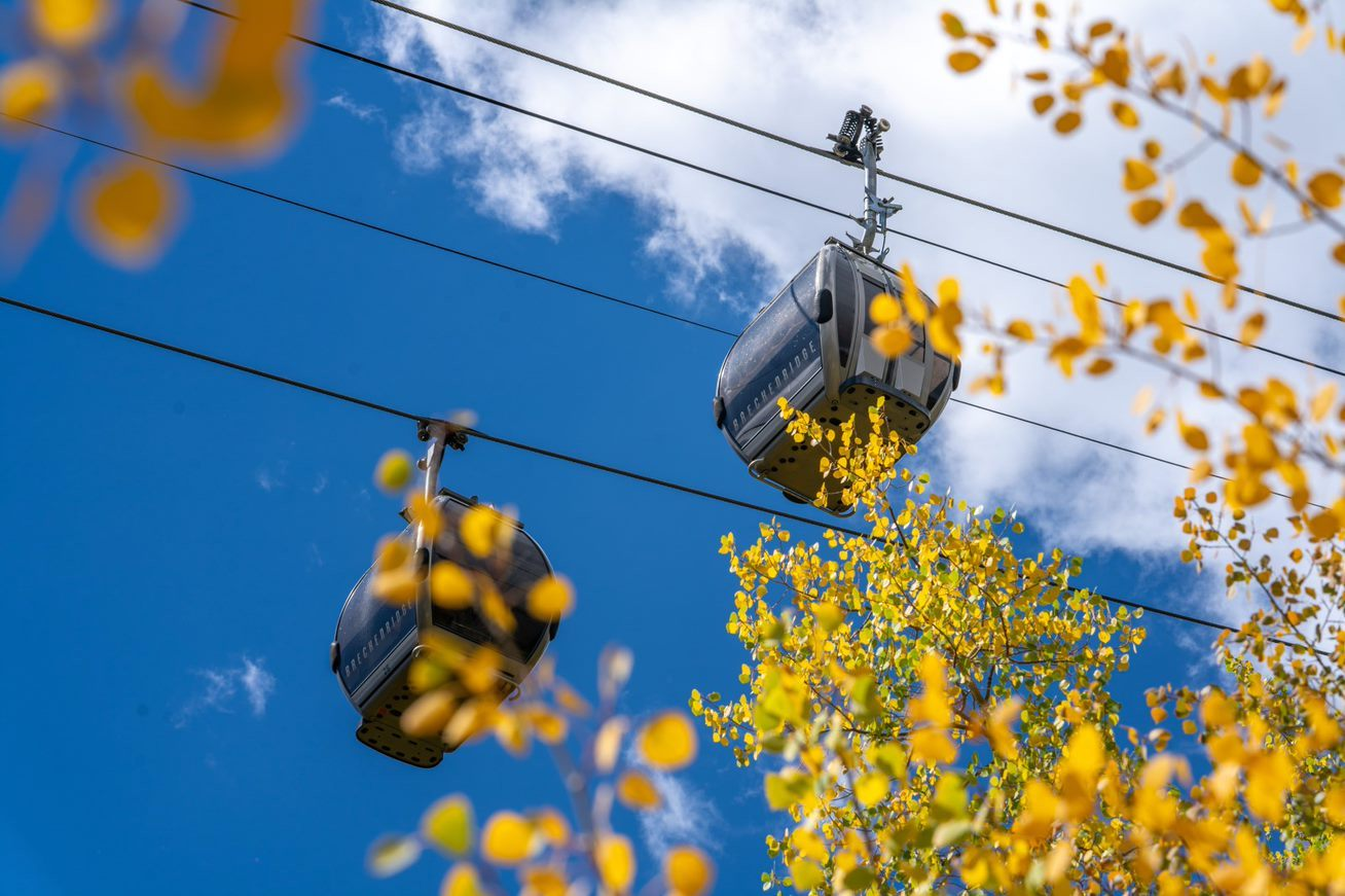Image of the BreckConnect Gondola seen through the yellowing leaves in Breckenridge, Colorado