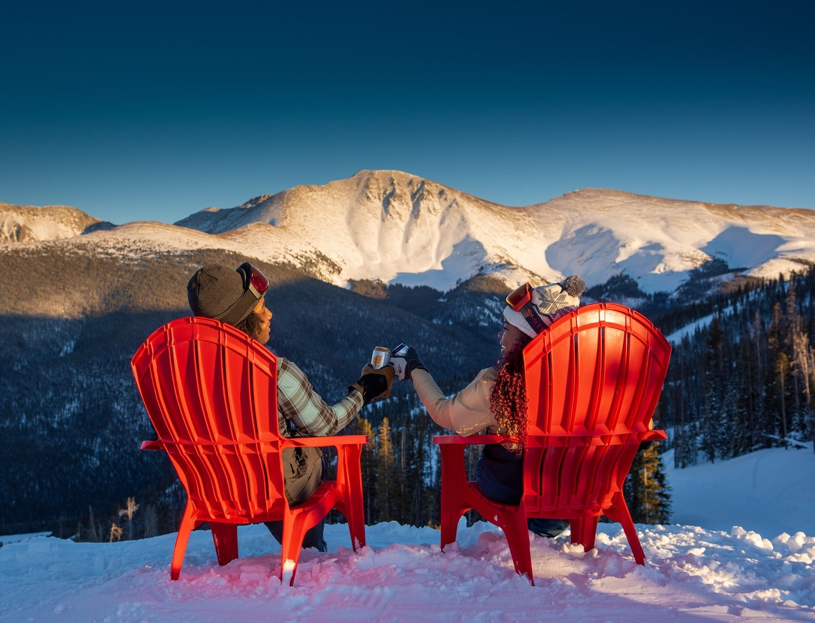 Image of people in red chairs looking out at the mountain while drinking a beer in Winter Park, Colorado